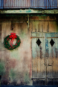 A Christmas wreath hangs next to old wooden doors in the French Quarter in New Orleans, Louisiana.