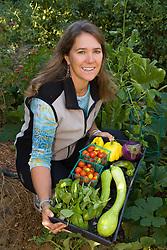 United States, California, Stockton, woman in garden holding harvest of vegetables MR