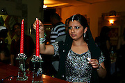 Jewish woman (of Indian ethnicity) lights the Shabat (Sabbath) candles on Friday night