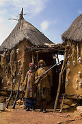 Hunter and wife pose with a riffle in front of their house decorated with dead animals and bones in Begnimato village. The Dogon Country is the most visited part of Mali with tourists visiting its tipical  villages that can be located on the cliff, on the sandy plain or in the rocky plateau