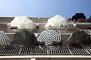 parasols hanging over the balcony of a flat building