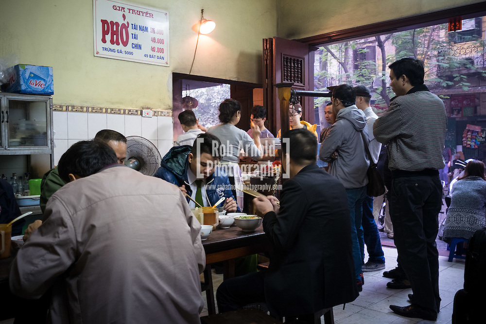 People tucking into their bowls of Pho Bo (beef noodle soup) at the iconic Pho Gia Truyen at 49 Bat Dan in Hanoi's Old Quarter.