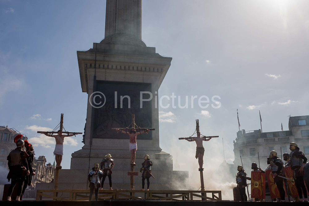 The final scenes of a suffering Jesus and two criminals being crucified on the cross at the base of Nelsons Column during The Passion of Jesus which is performed in Londons Trafalgar Square by members of Wintershall Trust on London, 25th March 2016: Played annually on Good Friday it celebrates the cruxifixion and resurrection of Jesus Christ. The cast re-enacts the Christian Biblical story to an audience of thousands and the main character is played by professional actor James Burke-Dunsmore. .