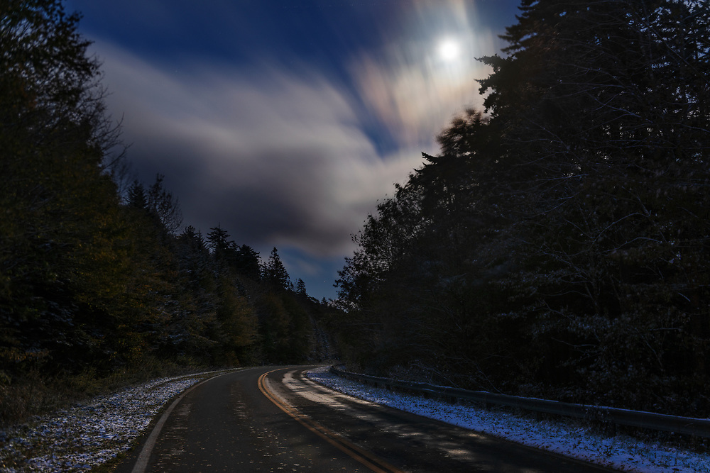 A nearly full moon illuminates passing clouds over a wintry Highland Scenic Highway in Pocahontas County, West Virginia.