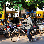 Old man looking to camera with bike in street of Panaji, India