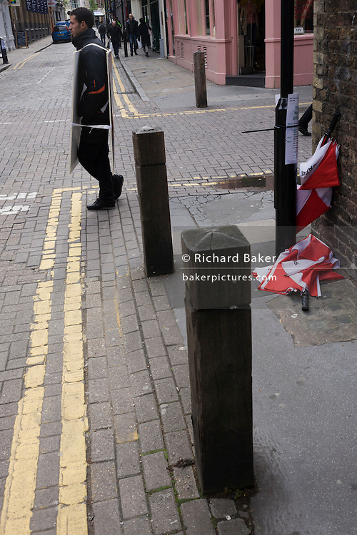 A Sandwich board man seemingly sandwiched by his own sign in a central London street.