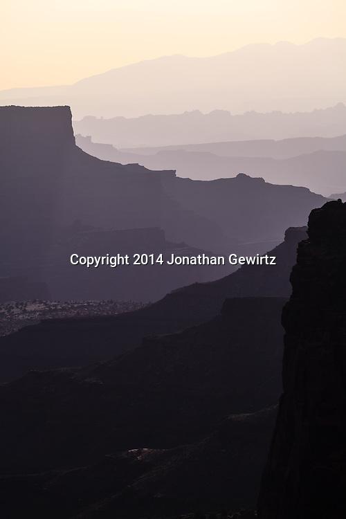 Morning view of Shafer Canyon backlit in hazy sunshine, Canyonlands National Park, Utah.<br /> <br /> WATERMARKS WILL NOT APPEAR ON PRINTS OR LICENSED IMAGES.<br /> <br /> https://tandemstock.com/assets/23621001