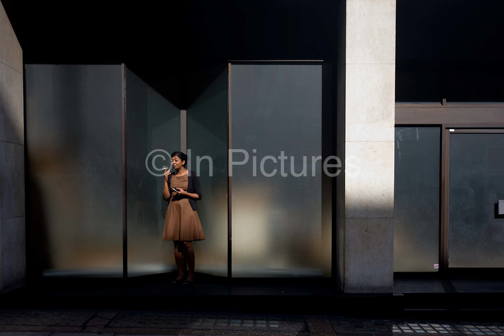 A young woman emerges from her London offices for a quiet smoke of her cigarette in a nearby doorway. Having taken a drag of her fag (an English slang term for a cigarette) Controversially, smokers appear to buy themselves more leisure time during a working day than others who are non-smokers, who don't leave their desks as often. Having chosen a favoured place, the woman enjoys the nicotine hit while enjoying the health benefits of autumn sunshine.