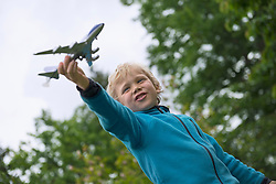 Young blonde boy playing with model airplane