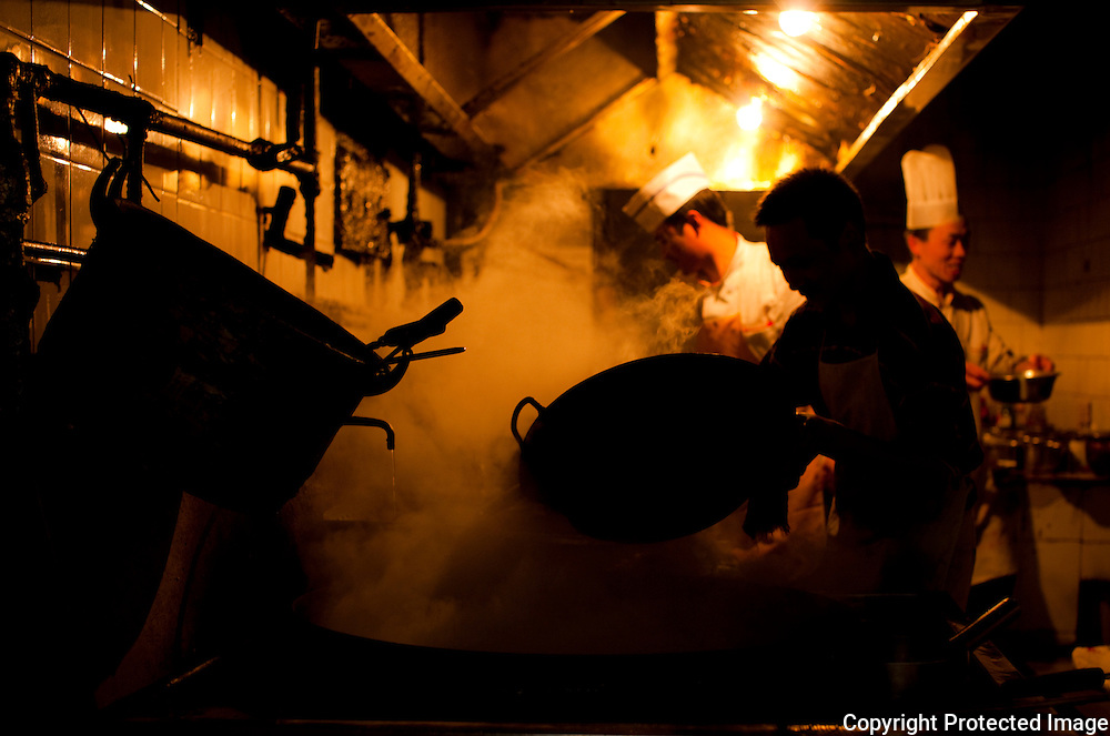 Cooks working in a steamy kitchen in Chengdu
