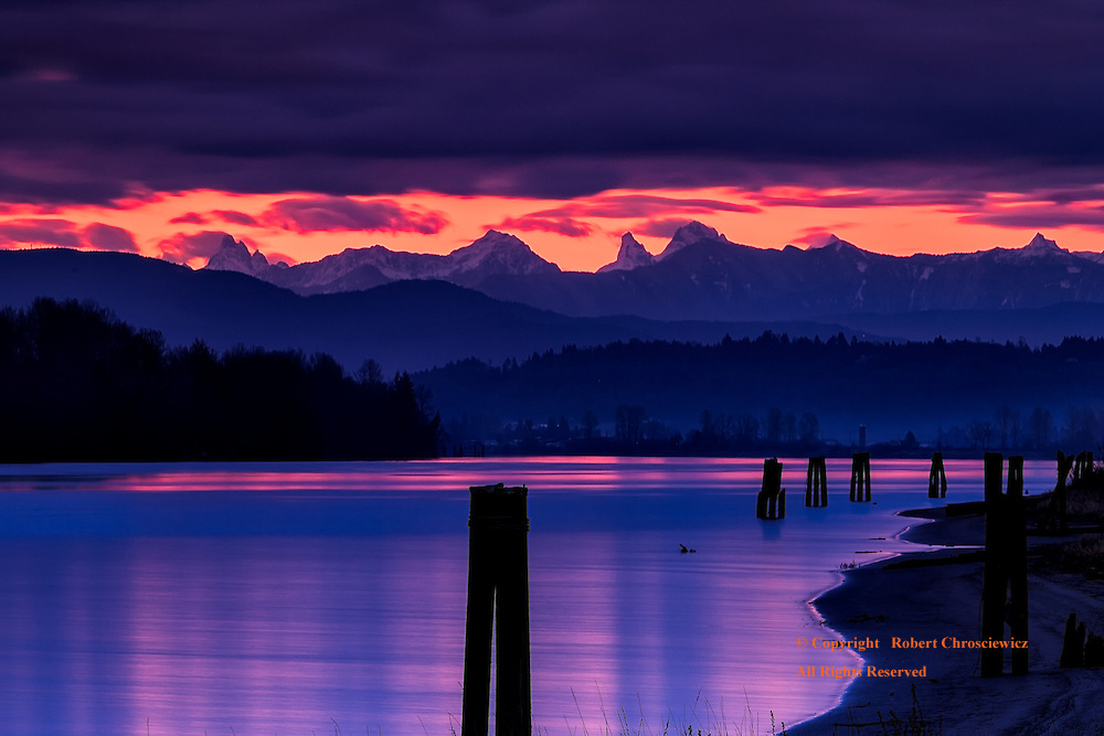 Fort Langley Morning: From the mighty Fraser River shoreline, clouds on the distant horizon part in a parallel long line, revealing mountains bathing in an orange sky, Fort Langley British Columbia Canada.