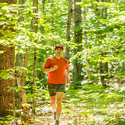 A man trail running in a forest in Jackson, New Hampshire.