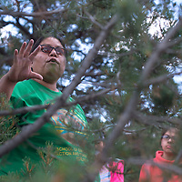 Lifetime weaver Janet Hoskie leads a walk through the woods at  Assayí Lake July 29 pointing out Juniper and other plants used to dye wool as a part of the Tséhootsooí Medical Center Youth Culture Retreat.