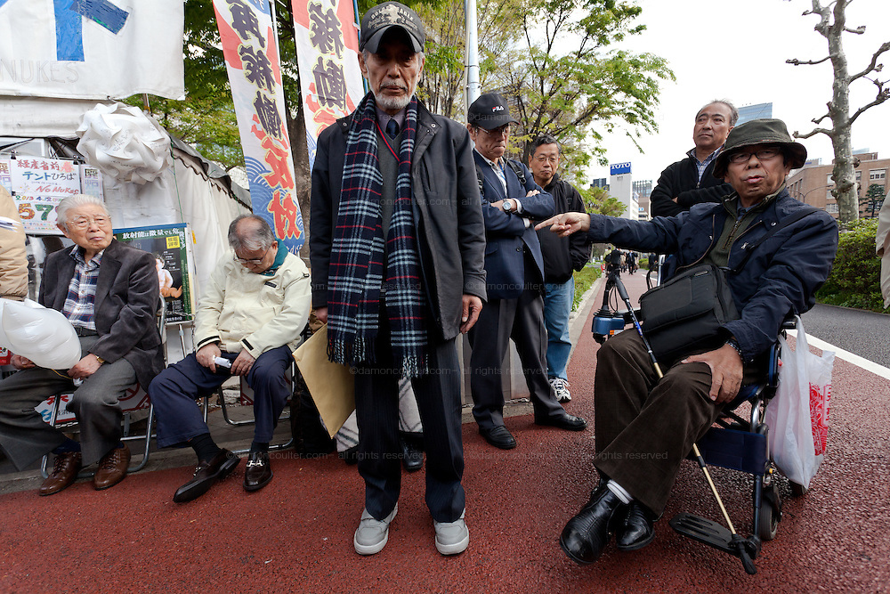 """Taro Fuchigami (left) (and Hiroaki Yamada (in wheelchair) talk to protesters after their meeting with METI officials at the Occupy Kasumigasaki Camp outside the METI building in Kasumigaseki, Tokyo, Japan. Friday April 12th 2013 The camp has been in place since September 2011 resisting several attempts to remove it. It now faces a court order restricting access and protestors have been served with a order to pay """"rent"""" for their use of the land."""