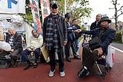 "Taro Fuchigami (left) (and Hiroaki Yamada (in wheelchair) talk to protesters after their meeting with METI officials at the Occupy Kasumigasaki Camp outside the METI building in Kasumigaseki, Tokyo, Japan. Friday April 12th 2013 The camp has been in place since September 2011 resisting several attempts to remove it. It now faces a court order restricting access and protestors have been served with a order to pay ""rent"" for their use of the land."