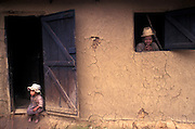 A mother and daughter occupy the window and doorway, the only openings to their mud hut in the Fianarantsua highlands. Locals do not have shoes and live in extreme poverty. This is one of the poorest countries in the world, and this one of its toughest regions,yet the people are happy, spirited and content.