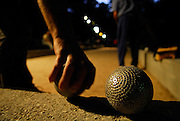 Close-up of balls used in Croatian game of Buce, players and rink in background. Makarska, Croatia