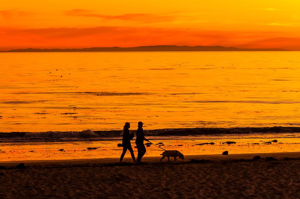 Women walking with a dog at sunset at Hendry's Beach (Arroyo Burro County Beach Park), Santa Barbara, California USA.