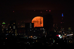© Licensed to London News Pictures. 29/03/2021. LONDON, UK.  A 99% waning gibbous moon rises over the buildings of central London.  This month's full moon is known as the Worm Moon according to the Old Farmer's Almanac, recognising that earthworms appear as the soil warms in spring. In addition, it is a Paschal Full Moon, being the first full Moon to occur after the spring equinox as well as a super moon.  Photo credit: Stephen Chung/LNP