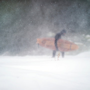 """Aurelien treks across the snow in near white-out conditions heading towards the open water of Lake Ontario. """"It really gets nasty, it gets extremely nasty, it gets extremely windy, and extremely cold. There is no visibility and that's when we have to surf because that's when there are waves. We are not talking about a groundswell, we are talking about a wind swell. Most of the time the windy day's come in the middle of winter."""""""