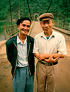 Two well dressed men standing in front of suspension bridge