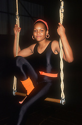 Teenage girl wearing leotard balancing on trapeze swing,
