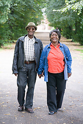 Older couple walking down an avenue of trees in the park together,