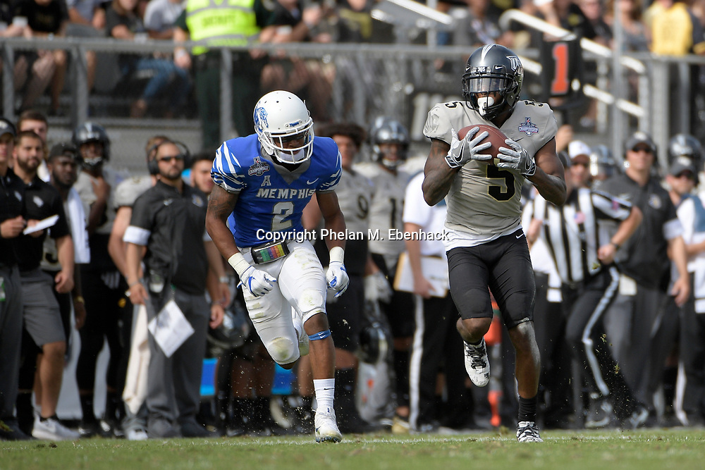 Central Florida wide receiver Dredrick Snelson (5) runs after catching a pass in front of Memphis defensive back Terrell Carter (2) during the first half of the American Athletic Conference championship NCAA college football game Saturday, Dec. 2, 2017, in Orlando, Fla. (Photo by Phelan M. Ebenhack)