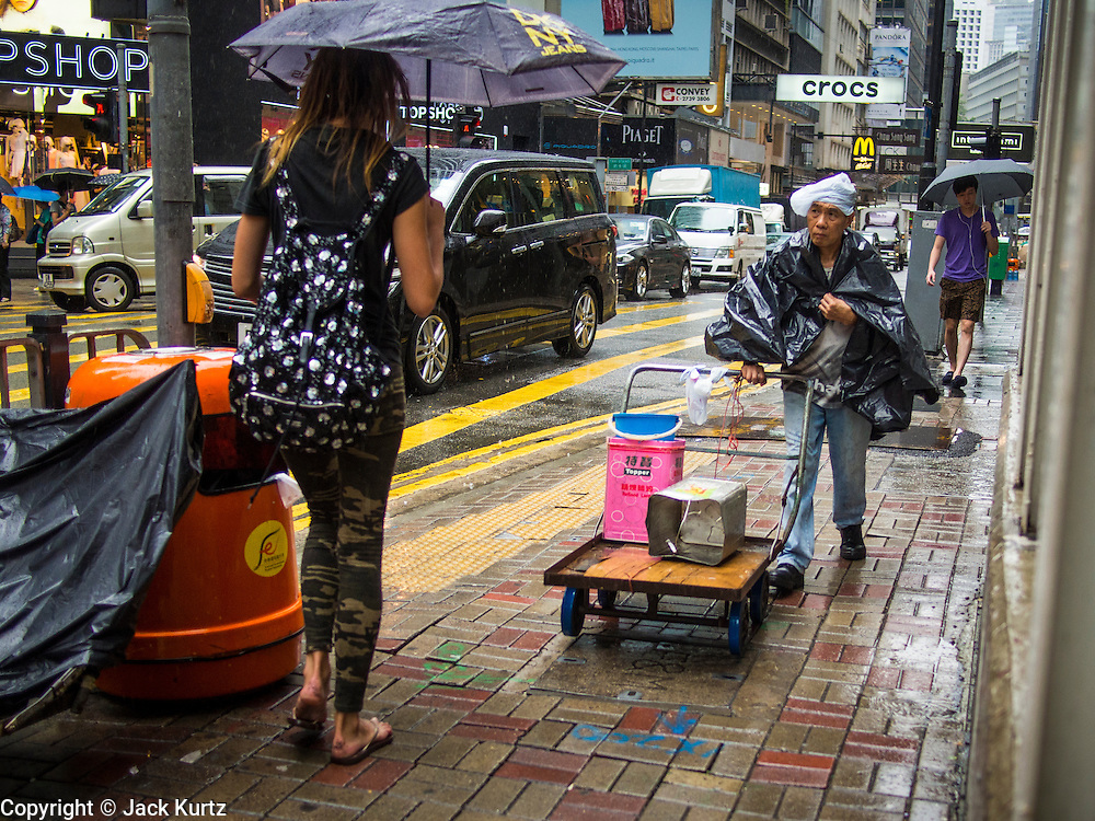 13 AUGUST 2013 - HONG KONG:  A Hong Kong man pushes a cart up a street during a break in the rains of Typhoon Utor. Typhoon Utor (known in the Philippines as Typhoon Labuyo) is an active tropical cyclone located over the South China Sea. The eleventh named storm and second typhoon of the 2013 typhoon season, Utor formed from a tropical depression on August 8. The depression was upgraded to Tropical Storm Utor the following day, and to typhoon intensity just a few hours afterwards. The Philippines, which bore the brunt of the storm, reported 1 dead in a mudslide and 23 fishermen missing at sea. The storm brushed by Hong Kong bringing several millimeters of rain and moderate winds to the island but causing no reported damage or injuries. It is expected to make landfall in China.  PHOTO BY JACK KURTZ