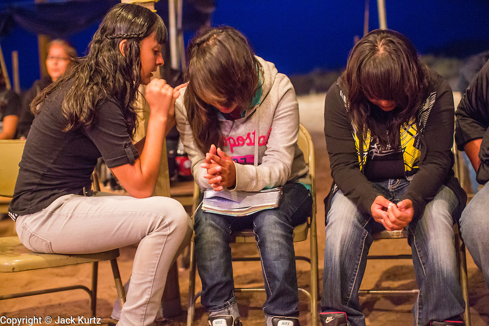 """13 JULY 2012 - FT DEFIANCE, AZ: Teenagers pray during the alter call at the 23rd annual Navajo Nation Camp Meeting in Ft. Defiance, north of Window Rock, AZ, on the Navajo reservation. Preachers from across the Navajo Nation, and the western US, come to Navajo Nation Camp Meeting to preach an evangelical form of Christianity. Evangelical Christians make up a growing part of the reservation - there are now more than a hundred camp meetings and tent revivals on the reservation every year. The camp meeting in Ft. Defiance draws nearly 200 people each night of its six day run. Many of the attendees convert to evangelical Christianity from traditional Navajo beliefs, Catholicism or Mormonism. """"Camp meetings"""" are a form of Protestant Christian religious services originating in Britain and once common in rural parts of the United States. People would travel a great distance to a particular site to camp out, listen to itinerant preachers, and pray. This suited the rural life, before cars and highways were common, because rural areas often lacked traditional churches.  PHOTO BY JACK KURTZ"""