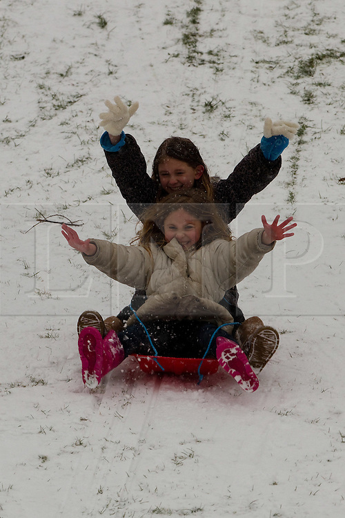 © licensed to London News Pictures. Manchester, UK  04/02/2012. Katie Wharnby and her older sister, Bethany Wharnby, play in the snow at Crossley Playing Fields in Chadderton, Manchester, as their parents, Martin Wharnby and Kelly Lee look on. Please see special instructions for usage rates. Photo credit should read Joel Goodman/LNP