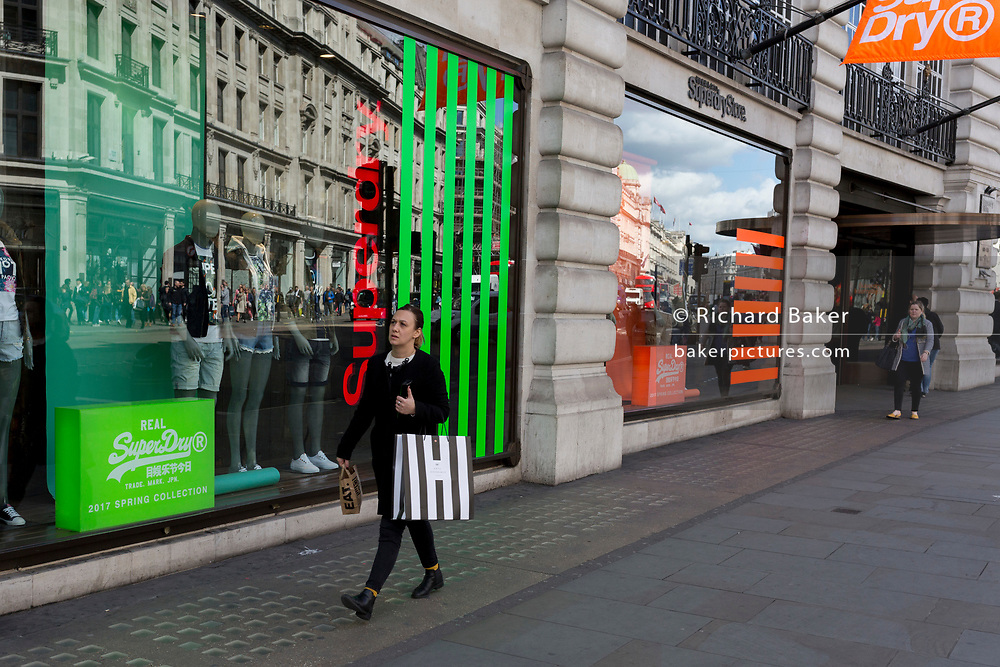 A lady shopper with a striped bag outside the window of fashion brand Superdry, on 18th April 2017, in London, England.