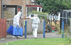 © London News Pictures. 29/07/2013. Manchester, UK. Police forensics officers outside a property (pictured) on  Delta Walk, in Moston, Manchester where A father has been stabbed to death and his 13-year-old child left in a critical condition. A second man, who also suffered stab wounds,  died after he crashed a hijacked car into a nearby pub. Photo credit Steve Allen/LNP