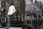 Shop window of famous tailors Gieves & Hawkes on Savile Row on 5th March 2021 in London, England, United Kingdom. Savile Row is a street in Mayfair, central London. Known principally for its traditional bespoke tailoring for men.