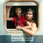 Passengers gaze out of the windows from the second class compartment. Many of them are interstate migrant workers traveling northward to Assam after earning money in the South. Others are more transitory, coming and going for just a few stops.<br /> Outside the Dibrugarh-Kanyakumari Vivek Express, the longest train route in the Indian Subcontinent. It joins Kanyakumari, Tamil Nadu, which is the southernmost tip of mainland India to Dibrugarh in Assam province, near the border with Burma.