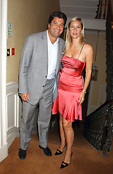 MR TIM MOUFARRIGE and his wife TV presenter TANIA BRYER at a party hosted by Dom Perignon and Vanity Fair magazine to celebrate the launch of a unique collection of essays based on the theme of seduction to raise money for the charity English Pen. The paty was held at the Dom Perignon Mallroom,  13 Grosvenor Crescent, London W1 on 8th September 2004.