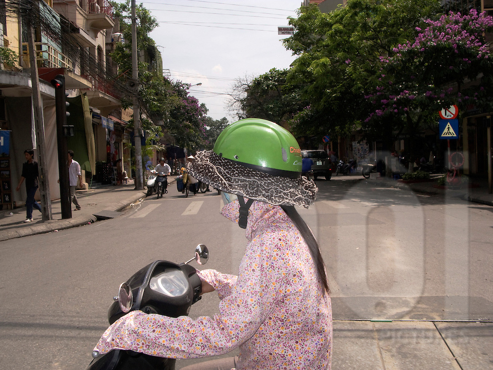 Vietnamese girl protects herself from the sun with a long sleeve shirt and a fancy green helmet, Hanoi, Vietnam, Southeast Asia