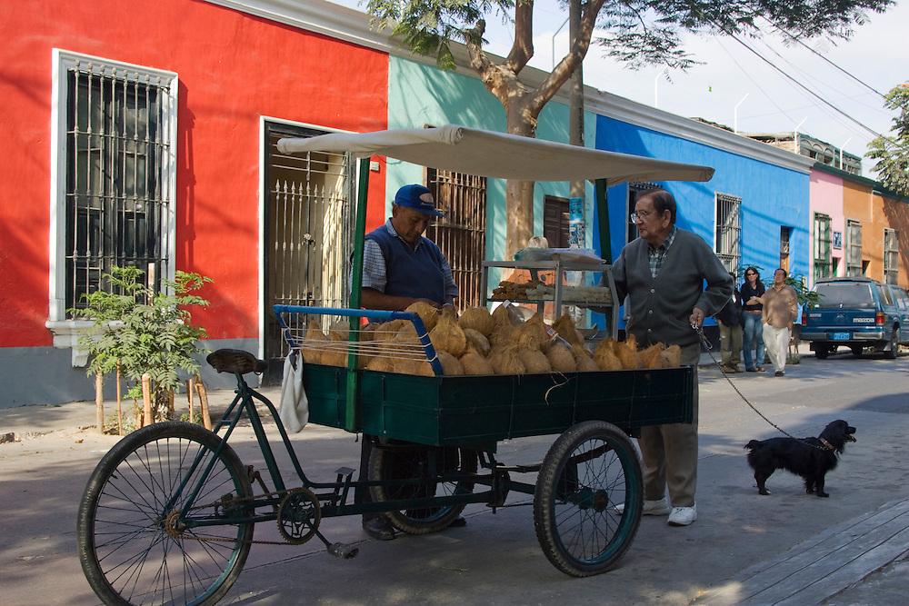 Coconut vendor on street with colorful houses in Barranco neighborhood, Lima, Peru, South America