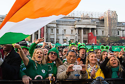 London, March 13th 2016. The annual St Patrick's Day Festival takes place in Trafalgar Square with performances on stage and plenty of Irish food and drink for the thousands of revellers.  PICTURED: A woman waves an Irish flag as performers whip up excitement in the crowd. ©Paul Davey<br /> FOR LICENCING CONTACT: Paul Davey +44 (0) 7966 016 296 paul@pauldaveycreative.co.uk