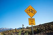 Een bord langs de Red Rock Canyon Road buiten Las Vegas geeft een bord aan dat fietsers op de vluchtstrook rijden. De weg is populair bij fietsers.<br /> <br /> A sign near Red Rock Canyon Road outside of Las Vegas says cyclists are sharing the road. The route is popular by cyclists.