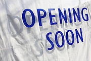 An Opening Soon sign announces a future new business is to offer new jobs, a symbol of recovering economic growth.