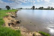 Nederland, Gennep, 20-8-2018 Bij Gennep wordt het talud van de brug, verkeersbrug, uitgegraven en vervangen door pijlers zodat het bij hoogwater beter doorstroomt. Dit talud vormt dan een flessenhals, obstakel voor het doorstromen . De Maasoevers moeten volgens RWS vrij zijn van obstakels en dus worden de bakenbomen niet meer vervangen . Deze bakenbomen op de oever zijn karakteristiek voor het landschap langs de rivier de Maas . De Maas krijgt de ruimte. Door de aanleg van natuurvriendelijke oevers ontstaat er een geleidelijke overgang van water naar land. Op veel plaatsen langs de meanderende maas zijn nevengeulen aangelegd om het water meer ruimte tegeven . Foto: Flip Franssen