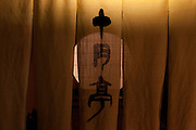 A name written in Kanji for a traditional moon door entrance to a tea house in the Higashi Chaya District geisha quarter of Kanazawa, Japan Sunday October 12th 2008