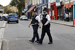 © Licensed to London News Pictures. 31/08/2020. London, UK. Police patrol in Portobello Road in Notting Hill, West London, on the day of the 2020 Notting Hill Carnival, which is being held virtually this year due to COVID-19 restrictions. Members of the public have been warned against congregating in the Notting Hill Area to celebrate the event. Photo credit: Peter Macdiarmid/LNP