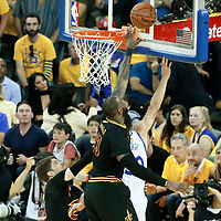 12 June 2017: Golden State Warriors guard Stephen Curry (30) goes for the layup between Cleveland Cavaliers guard Kyle Korver (26) and Cleveland Cavaliers forward LeBron James (23) during the Golden State Warriors 129-120 victory over the Cleveland Cavaliers, in game 5 of the 2017 NBA Finals, at the Oracle Arena, Oakland, California, USA.