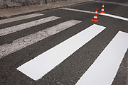 Two traffic cones prevent motorists driving over the half-finished paint job of fresh stripes on a zebra crossing, on 16th July, at Alcobaca, Portugal.