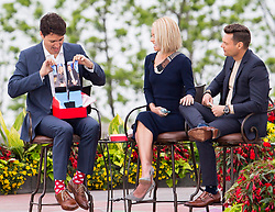 Prime Minister Justin Trudeau, left, holds up a pair of socks that he received as a gift from Kelly Ripa, centre, and Ryan Seacrest during his appearance on Live with Kelly and Ryan in Niagara Falls, Ontario on Monday, June 5, 2017. Photo by Aaron Lynett/CP/ABACAPRESS.COM    595507_012 Niagara Falls Canada