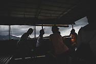 Hong Kong - September 1, 2019: On a local ferry connecting Lamma Island to Aberdeen on Hong Kong Island, passengers sit on benches and feel the strong wind.