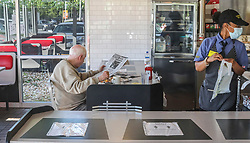 Waffle House's Tiffany (right) gets To Go orders ready as a seated guest has his meal (left) on Monday, April 27, 2020 at The Waffle House in Brookhaven, Ga. Restaurants around metro Atlanta began to reopen dining rooms Monday, April 27, 2020 as restrictions related to the coronavirus pandemic are lifted. Restaurants will be allowed to operate with in-person dining as long as they follow a set of 39 guidelines laid out by the state government, which include a requirement that all employees wear masks, a maximum of 10 customers per 500 square feet of floor space and a maximum of six diners per table. Photo by John Spink/Atlanta Journal-Constitution/TNS/ABACAPRESS.COM