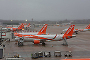 EasyJet Planes including an Airbus A320-214 WL  line up at the North terminal gates inside Gatwick Airport.  Gatwick Airport, Surrey, United Kingdom